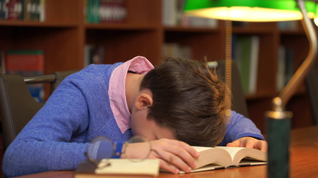 portrait of schoolboy doing their homework and sleeping on the book.