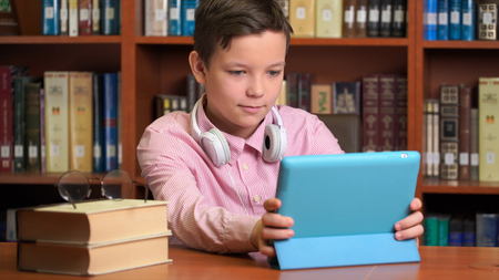 cute schoolboy using computer tablet and listening to it lecture