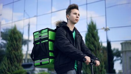 delivery man with green backpack rides a scooter through the city with food delivery