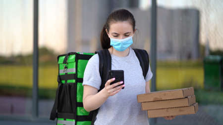 Young pizza courier is delivering an order. Delivery woman with phone holding cardboard boxes in medical mask. Zdjęcie Seryjne