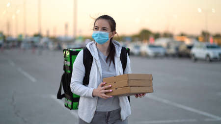 Young pizza courier is delivering an order. Delivery woman holding cardboard boxes in medical mask
