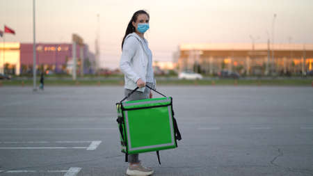 young courier wearing a medical mask is making a delivery of the order to the customers