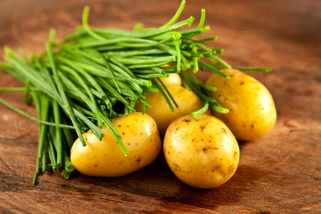 fresh potatoes and chives on wood