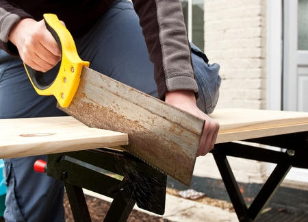 hands sawing wood photo