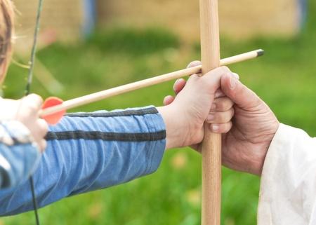 Close up of ein Kind gelehrt, Bogenschießen Standard-Bild - 10041076