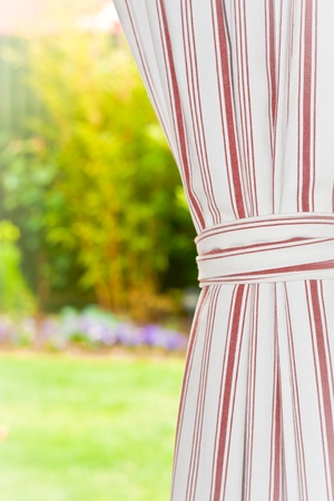A curtain with a garden in the background Stock Photo - 10040872