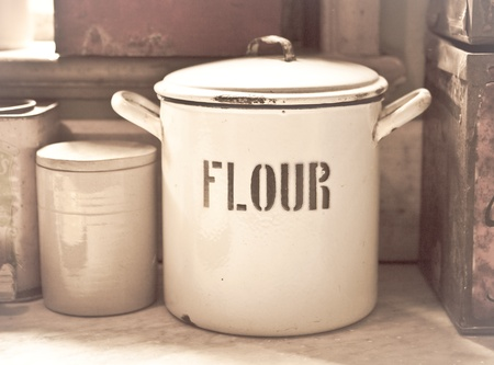collectibles: Vintage toned image of an enamel flour tin in an old style kitchen