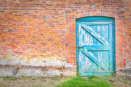 A quirky blue door set at an odd angle in a red brick wall in an English country garden Stock Photo