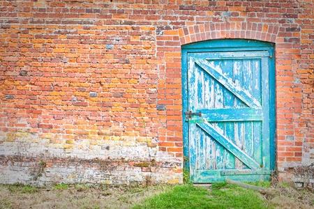 Eine schrullige blaue Tür in einem seltsamen Winkel in einen roten Ziegelmauer in einem englischen Land Garten Standard-Bild - 10179896