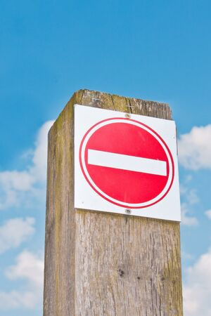 A red no entry sign against a bright blue sky photo