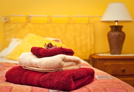 A pile of towels on a bed in a hotel room