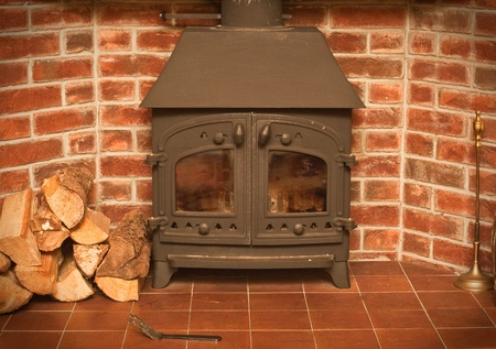 A wood burning stove in a red brick fireplace