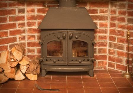 estufa: Una estufa de le�a en una chimenea de ladrillo rojo