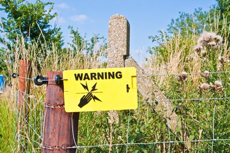 Warning sign for an electric fence in a rural settingÉ photo