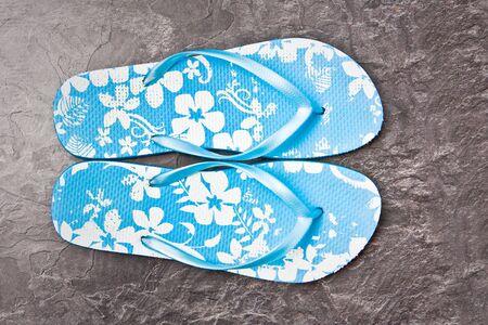 Nice blue flip flops on a slate surface Stock Photo - 10401275