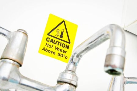 A bright yellow hot water warning notice behind a chrome tap photo