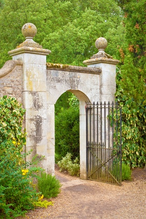 A nice gate in a stone wall in an english garden photo