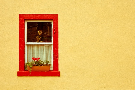 vibrant red window frame in a yellow wall photo