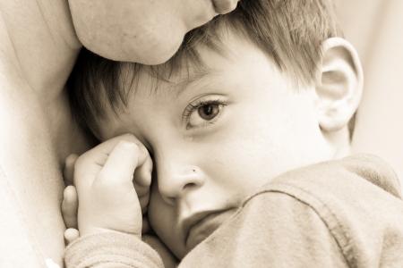 Schönes Bild einer jungen gestauchten Junge seiner Mama kuscheln