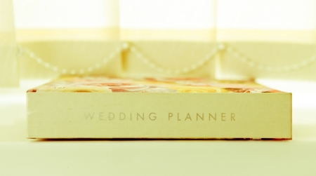 A wedding planner journal on a window sill in light airy colours