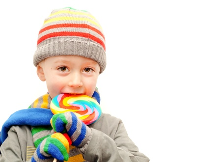 A young boy in winter clothes eating a colorful lollypop photo