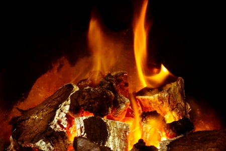 A burning log fire with glowing embers Stock Photo