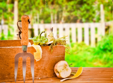Waste food items  for composting in a wooden crate on a garden table