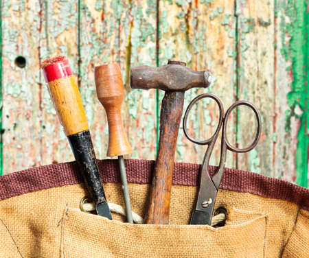 A selection of old work tools in a hessian bag photo