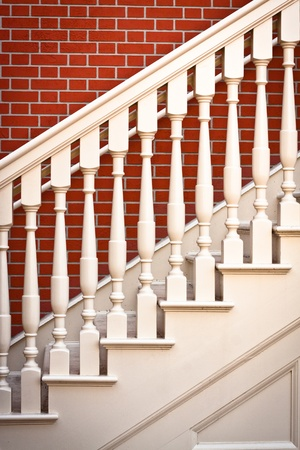 Background image of a traditional staircase against a red brick wall photo