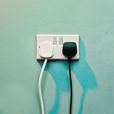 wall socket: Black and white electric plugs in a wall socket Stock Photo