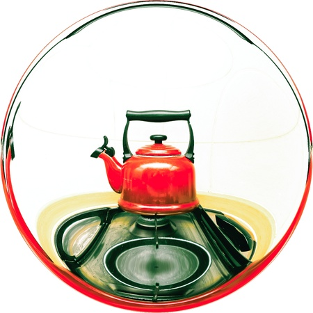 A traditional red whistling kettle on a gas hob photo