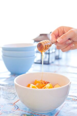 A womans hand pouring clear honey onto a bowl of fresh fruit salad photo