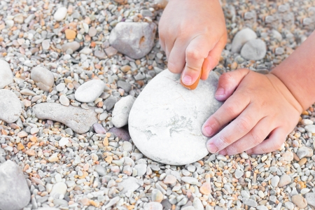 Close up of a young childs hands drawing on a stone photo