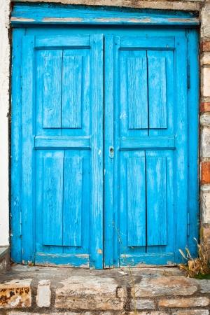 Old weathered blue door in a house in Greece Standard-Bild