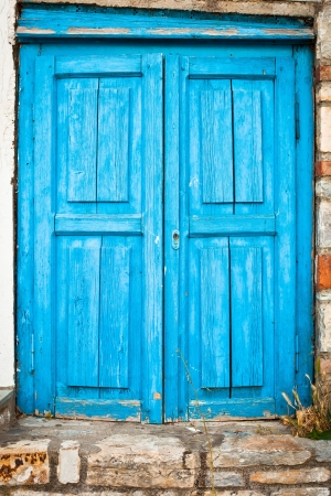 Old weathered blue door in a house in Greece Stock Photo