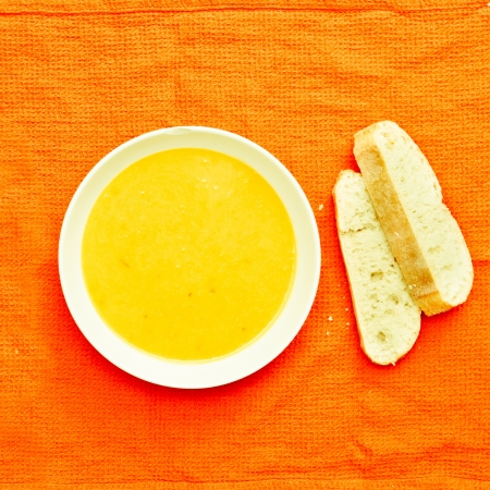 Butternut squash soup and fresh bread on a cloth photo