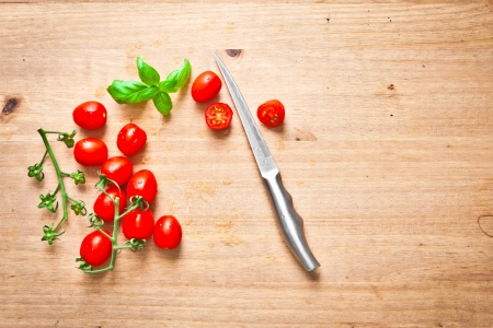 Fresh cherry tomatoes and basil on a chopping board photo