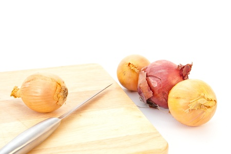 Onions ready for chopping with a metal knife, white background photo