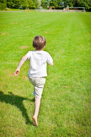 A young boy running across a playing filed photo