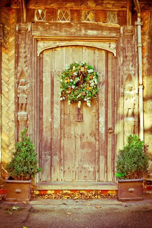 A decorative traditional christmas wreath on an old door photo