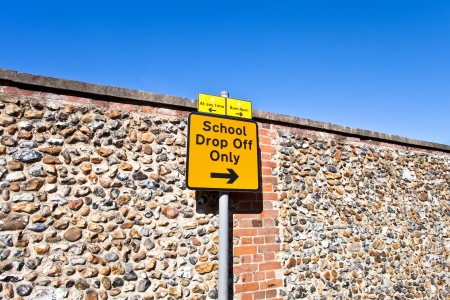 dropoff: A yellow school parking sign on a summer day in UK