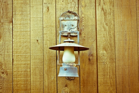 A nice vintage paraffin lamp mounted on a wooden wall photo