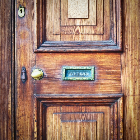 A wooden vintage front door with a letter box Standard-Bild