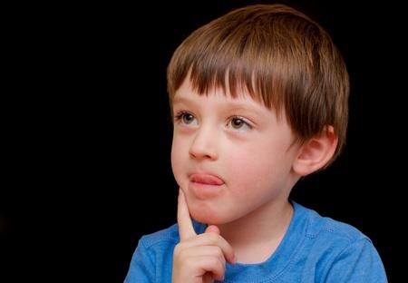 bambini pensierosi: Un curioso ragazzo di quattro anni, su uno sfondo nero