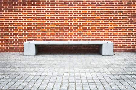 A modern stone bench against a brick wall with striking patterns photo