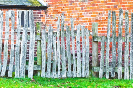 over grown: An old wooden picket fence against a red brick wall