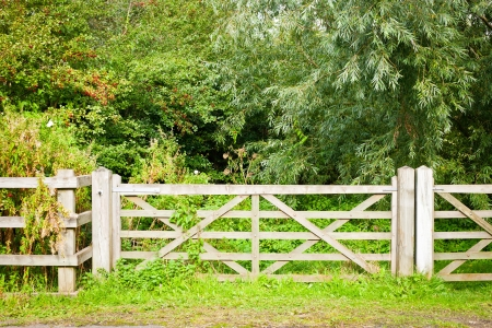 land locked: A wooden gate and fence in rural woodland Stock Photo