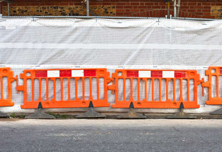 orange temporary boundary fencing at a construction site