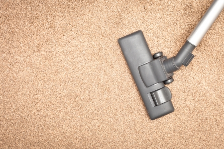 Head of a modern vacuum cleaner on a beige carpet