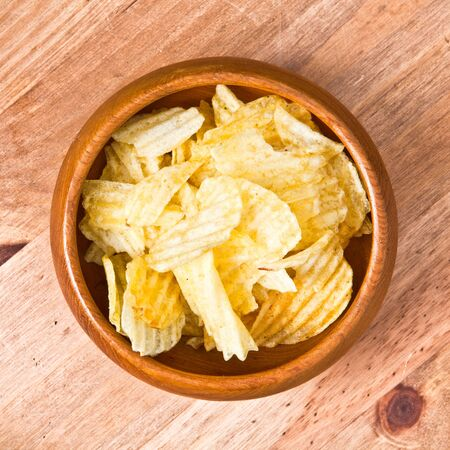 bowl of potato crisps on a wooden table photo